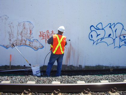 Worker removing graffiti from a wall