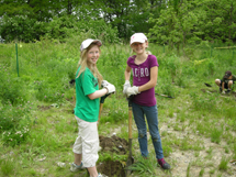 two young girls planting trees